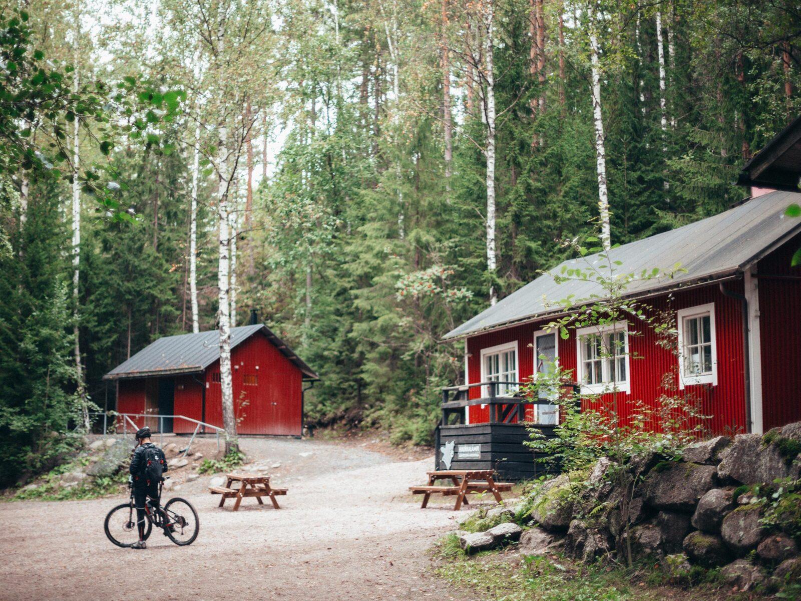 Cyklist vid stuga i skogen